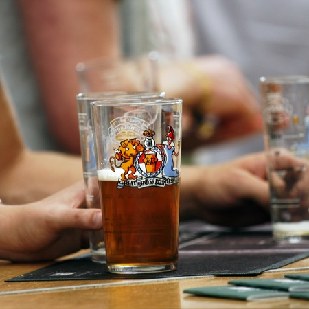 campaign for real ale: London, UK - August 17, 2013: The Great British Beer Festival, 2013, beer glass close-up, at Kensington Olympia, Britains biggest beer festival. Visitors can try wide range of real ales, ciders, perries and international beers.