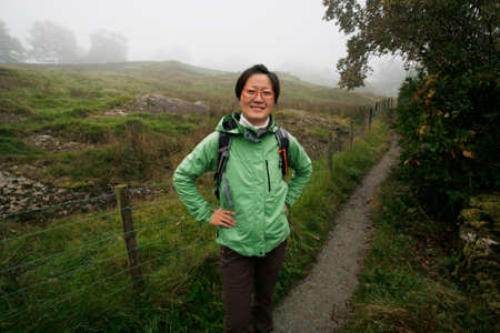 Smiling East Asian, misty morning,  Woman hiking in Lake District, Cumbria, UK.    Stock Photo - 24054112