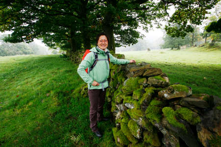 Smiling East Asian Woman hiking in Lake District, Cumbria, UK. Stock Photo - 24054114