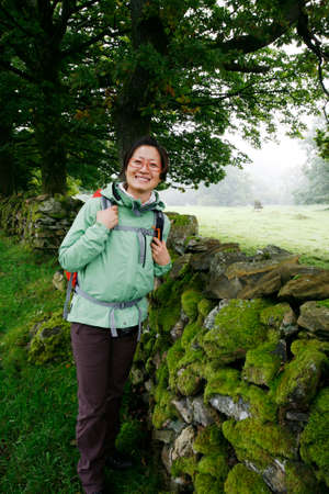 Smiling East Asian Woman hiking in Lake District, Cumbria, UK.    Stock Photo - 24054115