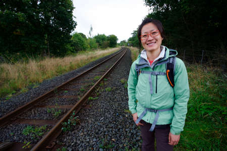 Smiling East Asian Woman hiking in Lake District, Cumbria, UK.    Stock Photo - 24054121