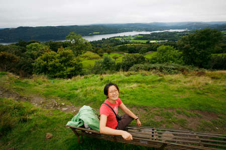 Smiling East Asian Woman, sit looking at the camera at the top of Orrest Head, hiking in Lake District, Cumbria, UK. Windermere lake is the far distance. Stock Photo - 24054116