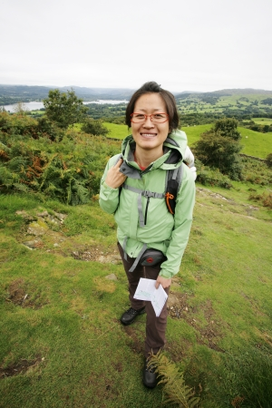 Smiling East Asian Woman hiking in Lake District, Cumbria, UK, Windermere lake in the far distance. Stock Photo - 24054122