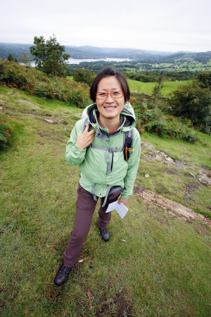 Smiling East Asian Woman hiking in Lake District, Cumbria, UK, Windermere lake in the far distance. Stock Photo - 24054123