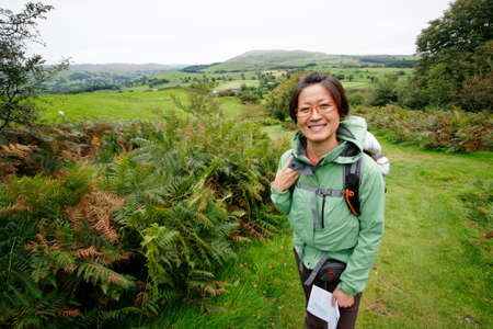 Smiling East Asian Woman hiking in Lake District, Cumbria, UK.    Stock Photo - 24054124