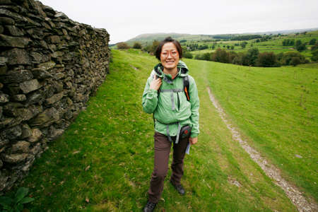Smiling East Asian Woman hiking in Lake District, Cumbria, UK.    Stock Photo - 24054104
