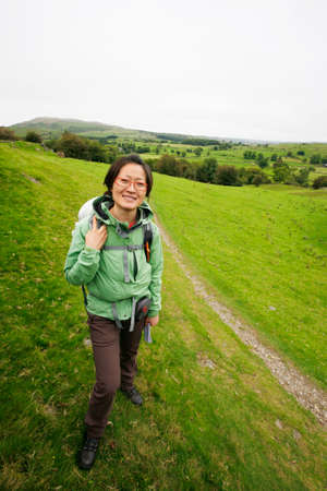 Smiling East Asian Woman hiking in Lake District, Cumbria, UK.    Stock Photo - 24054105