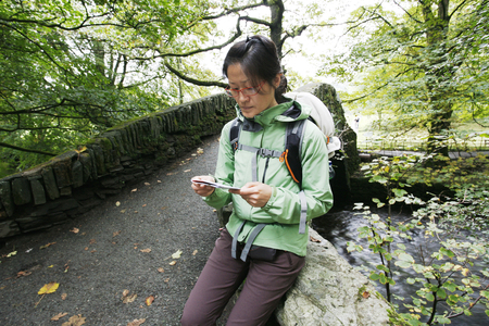 An East Asian Woman, reading a map, hiking in Lake District, Cumbria, UK.    Stock Photo - 24054107