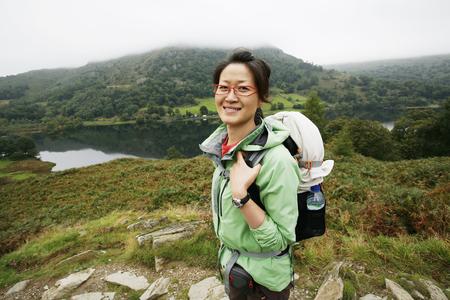 asian travel: Smiling East Asian Woman hiking in Lake District, Cumbria, UK.