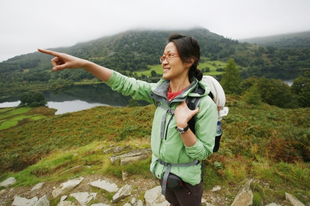 An East Asian Woman, pointing the direction, hiking in Lake District, Cumbria, UK. Stock Photo - 24054110