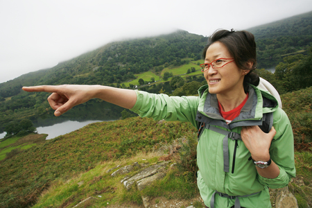 An East Asian Woman, pointing the direction, hiking in Lake District, Cumbria, UK. Stock Photo - 24054111