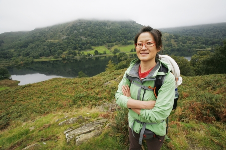 Smiling East Asian Woman hiking in Lake District, Cumbria, UK.    Stock Photo - 24054125