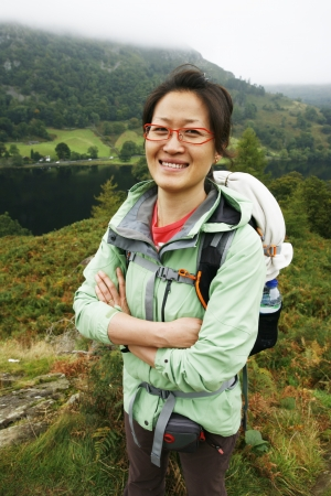 Smiling East Asian Woman hiking in Lake District, Cumbria, UK.    Stock Photo - 24054126