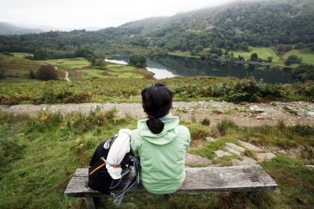 An East Asian Woman, sit on a bench looking down the Rydal Water, Lake District, Cumbria, UK. Stock Photo - 24054127