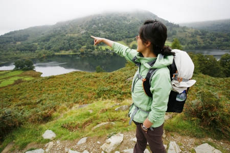 An East Asian Woman, pointing the direction, hiking in Lake District, Cumbria, UK. Stock Photo - 24054131