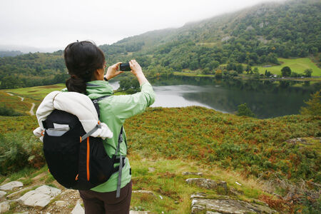 An East Asian Woman, taking pictures, hiking in Lake District, Cumbria, UK. Stock Photo - 24048334