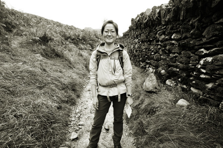 Smiling East Asian Woman hiking in Lake District, Cumbria, UK.    Stock Photo - 24048136