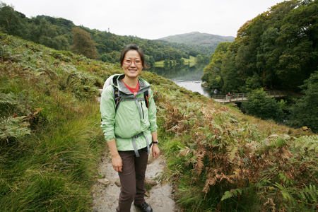 Smiling East Asian Woman hiking in Lake District, Cumbria, UK. Grasmere lake in the back ground. Stock Photo - 24054151