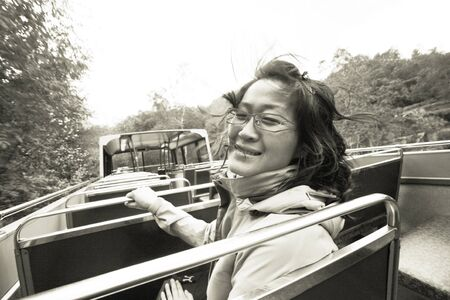 An East Asian Woman, hair blown by wind, on a tour bus, Lake District, Cumbria, UK.    photo