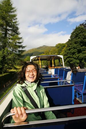Smiling East Asian Woman on a tour bus, Lake District, Cumbria, UK.    Stock Photo - 24054154