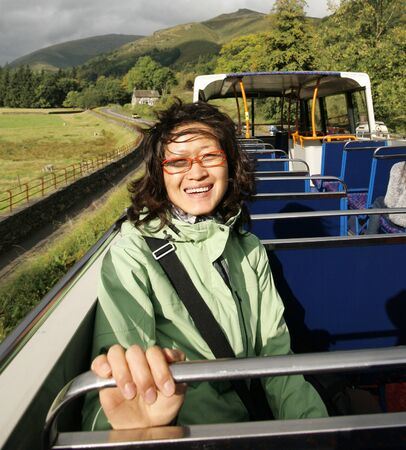Sonrisa de la mujer del este de Asia en un autob�s tur�stico, Lake District, Cumbria, Reino Unido. photo