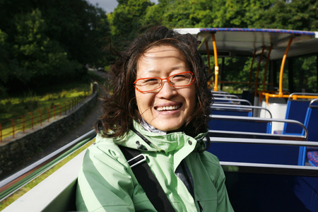 Smiling East Asian Woman on a tour bus, Lake District, Cumbria, UK.    Stock Photo - 24054156