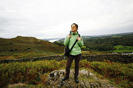 An East Asian Woman, stand on the lock, looking off into distance, hiking in Lake District, Cumbria, UK. Grasmere lake in the back ground.     Stock Photo - 24054157