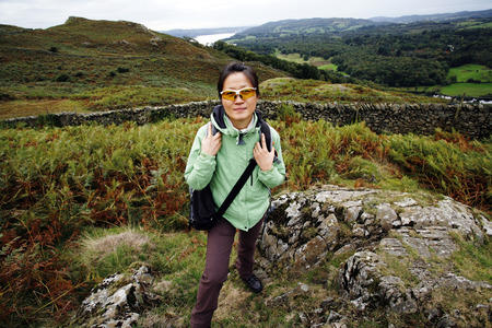 An East Asian Woman, looking at the camera, hiking in Lake District, Cumbria, UK. Grasmere lake in the back ground. Stock Photo - 24054158