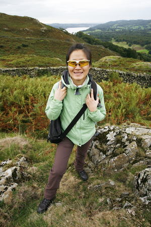 An East Asian Woman, looking at the camera, hiking in Lake District, Cumbria, UK. Grasmere lake in the back ground. Stock Photo - 24054159