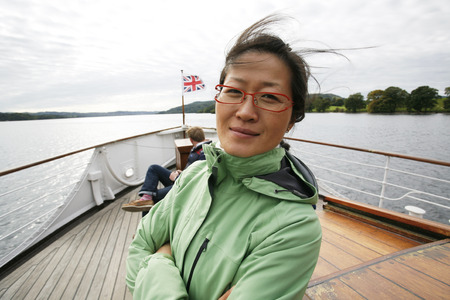 wind blown hair: An East Asian Woman, hair blown by wind, looking at camera, on a tour boat, Windermere, Lake District, Cumbria, UK.    Stock Photo
