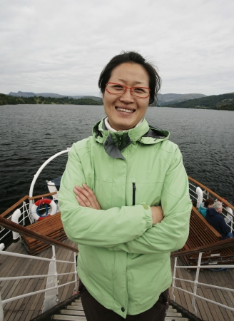Smiling East Asian Woman on a tour boat, Windermere, Lake District, Cumbria, UK. Stock Photo - 24054161