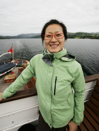 Smiling East Asian Woman on a tour boat, Windermere, Lake District, Cumbria, UK.    Stock Photo - 24054162