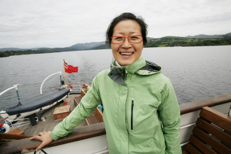 Smiling East Asian Woman on a tour boat, Windermere, Lake District, Cumbria, UK. Stock Photo - 24054163