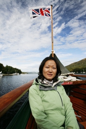 An East Asian Woman, looking at camera, Union Jack flag in the back ground, on a tour boat, Windermere, Lake District, Cumbria, UK. Stock Photo - 24048407