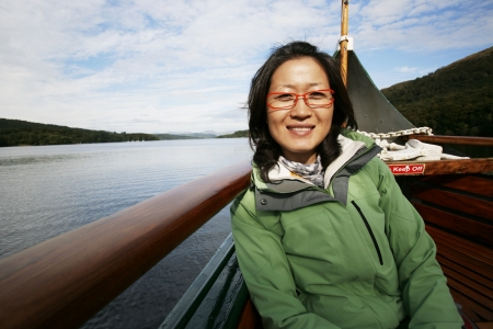 Smiling East Asian Woman on a tour boat, Windermere, Lake District, Cumbria, UK.    Stock Photo - 24048201
