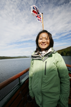 Smiling East Asian Woman, union jack flag in the back ground, on a tour boat, Windermere, Lake District, Cumbria, UK. Stock Photo - 24048403