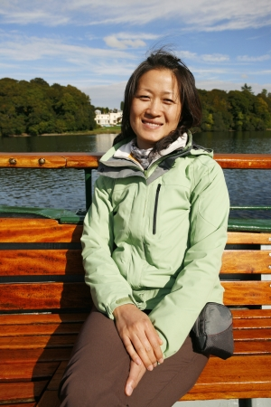 Smiling East Asian Woman on a tour boat, Windermere, Lake District, Cumbria, UK.    Stock Photo - 24054202