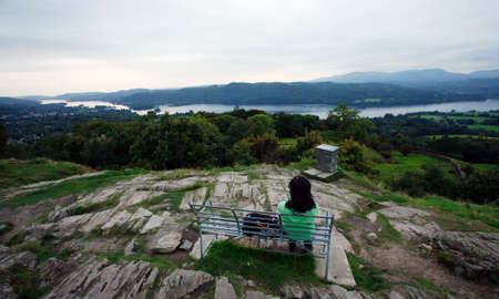 A Woman sit on a bench looking over the Windermere Lake from the top of Orrest Head.   photo