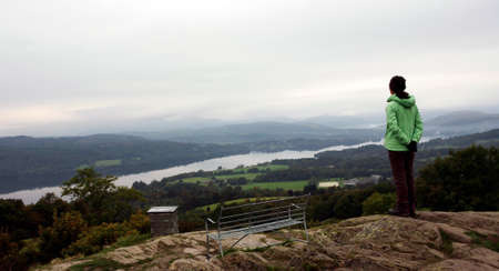 A Woman stand looking over the Windermere Lake from the top of Orrest Head.    photo