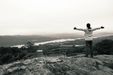 A Woman stand, raised hands, looking over the Windermere Lake from the top of Orrest Head.   photo