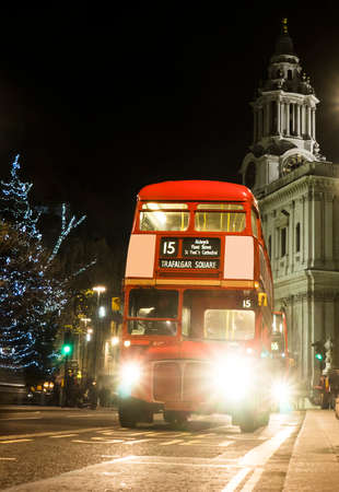 Londons iconic Routemaster Bus at dusk and St Pauls Cathedral is in the background.