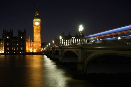 westminster city: Big Ben, bus lights trail present, seen from Westminster Bridge at Night Stock Photo