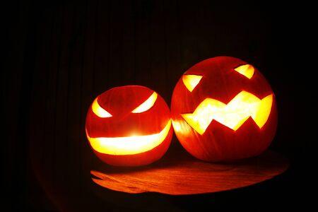 hollows: closeup of scary halloween pumpkins on black dark background Stock Photo