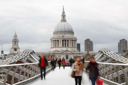 st pauls: People walking on millennium bridge, St Pauls Cathedral, locates at the top of Ludgate Hill in the City of London, in the back ground