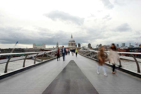 millennium bridge: People walking on millennium bridge, St Pauls Cathedral, locates at the top of Ludgate Hill in the City of London, in the back ground