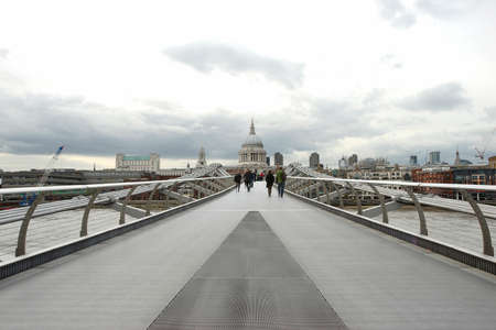 city of london: People walking on millennium bridge, St Pauls Cathedral, locates at the top of Ludgate Hill in the City of London, in the back ground