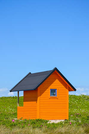 brightly colored orange beach house in the grass under a blue sky Stock Photo