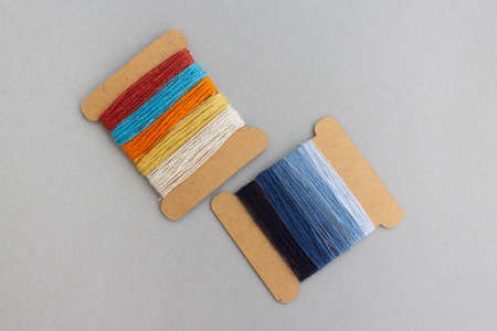 palette of blue and multicolored spool of threads for jeans custom work on light grey background