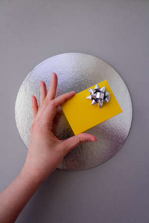Woman hand holding yellow gift box with silver bow on grey background with a silver circle compositional center. Flat lay style. Festive greeting concept. Vertical view