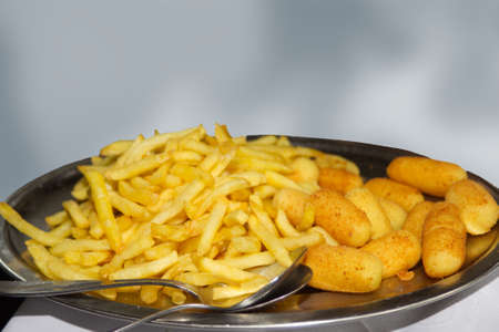 French fries and croquettes on plate in restaurant isolated